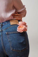 Perfect woman's bottom in a blue jeans and fresh roses living coral color in a back pocket on a light gray background, place for text. Congratulation card.