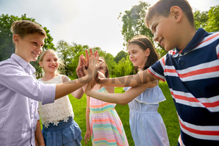 group of happy kids making high five outdoors