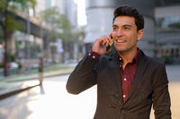 Young happy Hispanic businessman thinking while talking on the phone outdoors