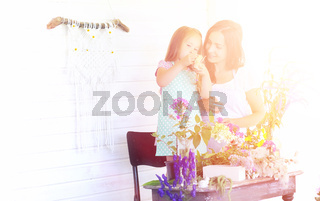 A young girl with a daughter is picking up a bouquet. A young mo