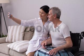 Nurse taking selfie with elderly patient.