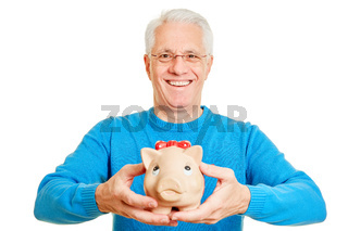 Rentner hält Sparschwein als Altersvorsorge