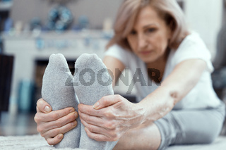 Charming mature woman touches toes. Yoga exercise