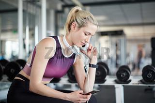 Frau im Fitnesscenter schaut auf Smartphone