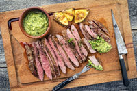 Barbecue dry aged wagyu flank steak with pineapples and chimichurri sauce as top view on a cutting board