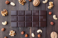 Delicious dark chocolate and nuts on wooden background