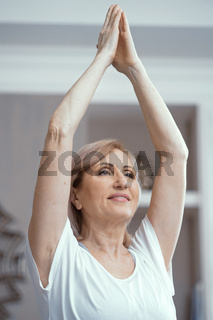 Beautiful woman holds hands pressed together above head