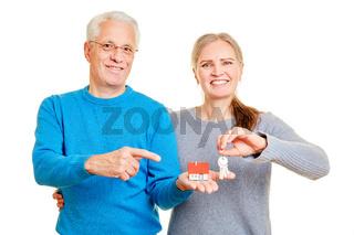 Paar Senioren mit Haus und Schlüssel