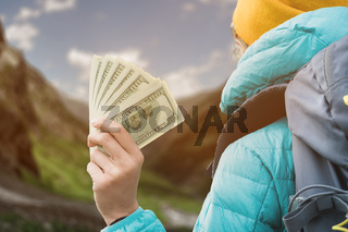 A traveler girl wearing a hat and sunglasses is holding a hundred dollar bills in the hands of a fan against the backdrop of cliffs on nature. Back view