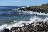 Wellen brechen sich an den Lavafelsen der Küste