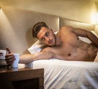 Sexy naked young man on bed with cup