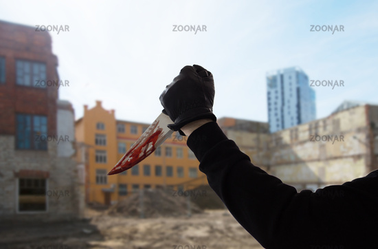 hand in glove with blood on knife over city ruins