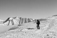 Skier on top of ski slope at nice winter morning
