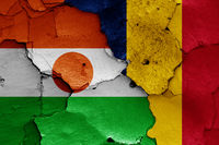 flags of Niger and Chad painted on cracked wall
