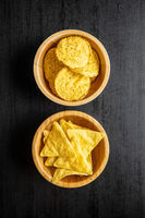 Round and triangular nacho chips. Yellow tortilla chips