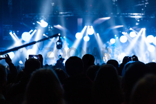 Silhouette of a concert crowd. The audience looks towards the stage.