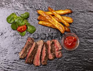 Steakscheiben mit Pommes Frites auf Schiefer