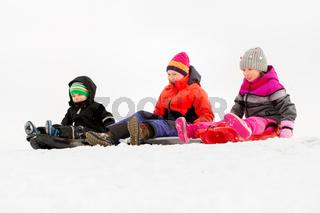 happy little kids sliding on sleds in winter