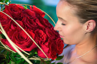 A woman with a romantic face sniffs at the red rose.