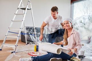 Junges Paar beim Tapezieren und Malern