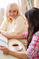 Senior mother and daughter read a book over a cup of tea