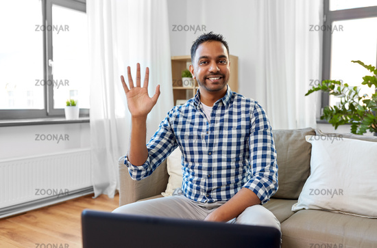 indian male blogger waving hand at home