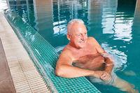 Senior Mann entspannt sich im Schwimmbad