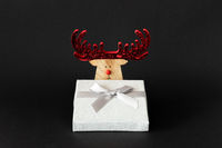Christmas decoration reindeer with silver gift box on a black background with space for your content
