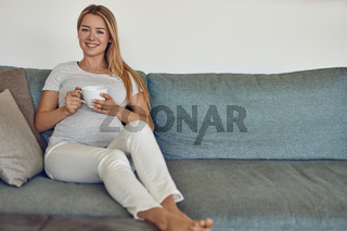 Pretty young pregnant woman relaxing on a couch