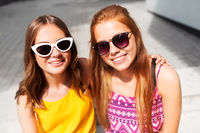 smiling teenage girls in sunglasses outdoors