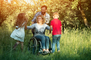 Children run to their disabled mother in the park