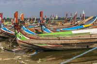 Colourful boats at U Bein Bridge on sunny day in Mandalay, Myanmar
