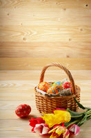 Easter eggs in wicker basket and colorful tulip flowers on wooden table background with space for text
