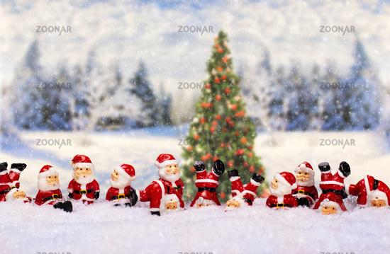 Weihnachtsmänner vor Winterlandschaft mit Weihnachtsbaum