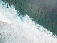 Aerial shot of the braking wave in the ocean.
