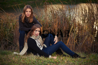 Two young fashion girls in black pullover and dark blue jeans outdoor