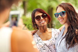 woman photographing her friends in summer park
