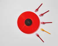 Red vinyl record with plastic colorfut forks on a gray background.