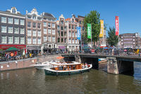 Tourists making sightseeing trip by launch ship in Amsterdam canals