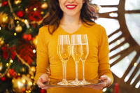 Happy woman holding a glasses of champagne on silver tray