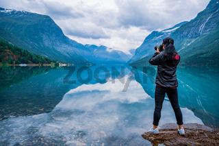 Nature photographer tourist with camera shoots lovatnet lake Beautiful Nature Norway.