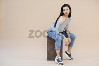 Beauty portrait of sensual asian young woman with dark long hair in cozy knitted grey sweater on the beige background