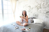 Cheerful sad young craing woman eating sweets in her bedroom
