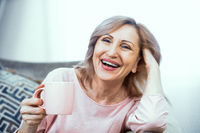 Happy mature woman with cup of tes in her hands