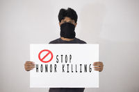 Young man protesting against the Honor Killing by holding Placard showing of Stop Honour Killing on isolated background