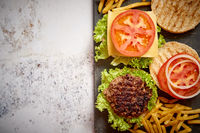 Two tasty grilled home made burgers with beef, tomato, onion and lettuce