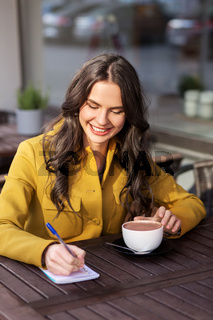 happy woman with notebook drinking cocoa at cafe