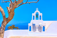 Old white belfry and dry tree in Santorini