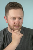 Bearded casual man with hand on his chin