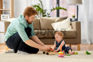 father and baby playing with toy blocks at home